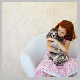 Girl (10-11) Sitting in a Chair and Holding a Poodle --- Image by © Royalty-Free/Corbis